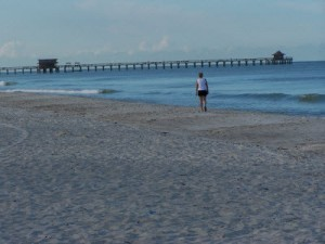Beach photo whith Naples pier in background and person walking